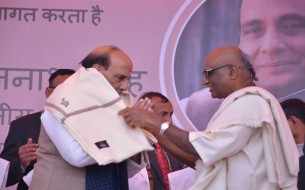 Madhu Pandit Dasa, Chairman felicitating Sri Rajnath Singh, Minister of Home Affairs, with a shawl on stage