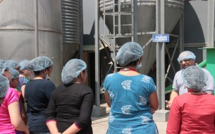 Anilkumar T.B. explaining to the group of volunteers, how the Rice Master Silo at this gravity-flow-based kitchen works
