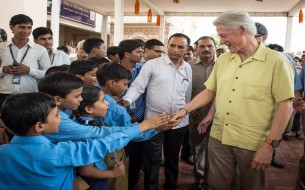 An excited bunch of kids shakes hands with US Ex-President. Photo credit: Clinton Foundation/ Barbara Kinney